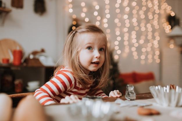 Lief klein meisje in rood gestreepte pyjama zit in een mooie keuken versierd met een slinger