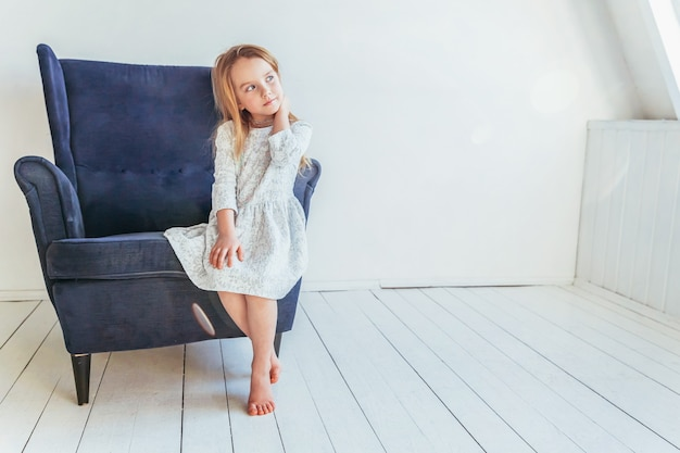 Lief klein meisje in witte jurk zittend op moderne gezellige blauwe stoel ontspannen in witte lichte woonkamer thuis binnenshuis. jeugd schoolkinderen jeugd ontspannen concept.