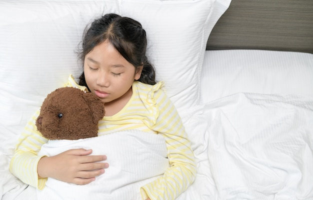 Lief klein meisje slaapt met een teddybeer in haar bed thuis, zoete droom en rust concept
