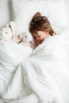 Lief klein meisje slapen in wit bed met konijn speelgoed in de buurt van haar