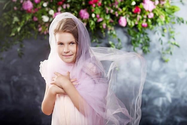 Lief klein meisje speelt met lichte stof tegen de bloemen. portret van het aardige kleine meisje.