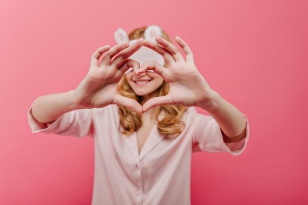 Lief meisje dat in oogmasker hartteken toont. binnenportret van glimlachende krullende vrouw in zijden pyjama die op roze muur met haar handen op voorgrond wordt geïsoleerd.