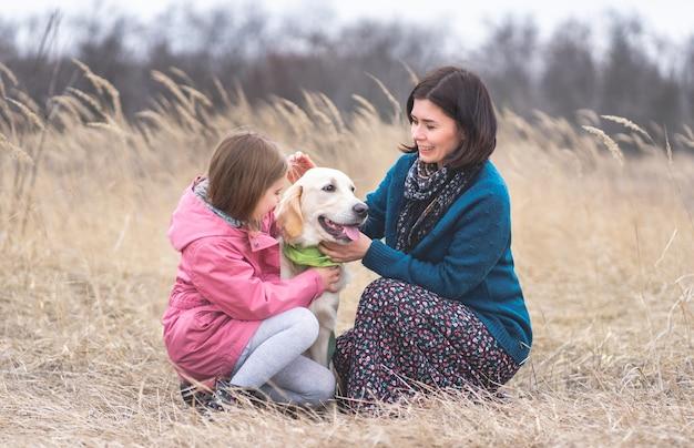 Lief meisje en vrouw die mooie hond buiten aaien