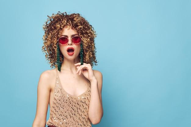 Lief meisje handgebaren op een blauwe achtergrond, een rode zonnebril en een hart