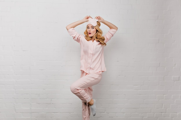 Lief meisje in grijze sokken dansen in de buurt van dichtgemetselde muur. verraste mooie dame in eyemask en zijden pyjama's die zich voordeed op een witte muur.