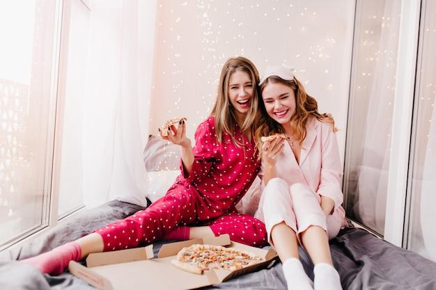 Lief meisje in trendy rood nachtkostuum genieten van kaas pizza met zus. glimlachende prachtige dames die ochtend in bed doorbrengen met fastfood.