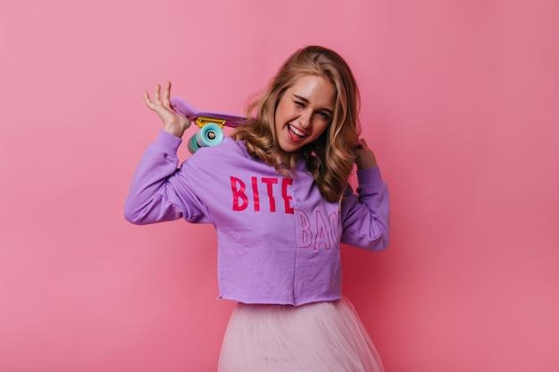 Lief meisje met schattig roze skateboard glimlachen naar de camera. portret van geïnteresseerd vrouwelijk model in paars overhemd.