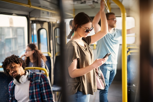 Lief meisje met zonnebril in het gebruik van de telefoon terwijl je in een bus.
