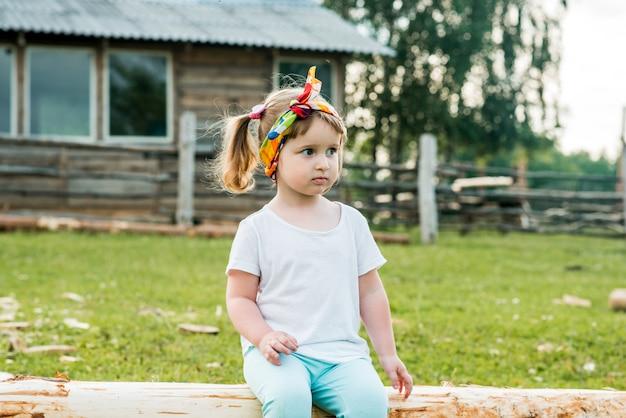 Lief mooi kind, meisje zittend op een hek in het dorp. wandelingen op het platteland. landbouw.