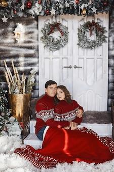 Lief paar geliefden in kerstkleren poseren in een met kerst versierd interieur