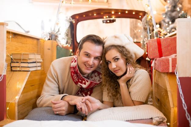 Lief plezier hebben en samen genieten van hun tijd in een pick-up auto. kerstverlichting op de achtergrond