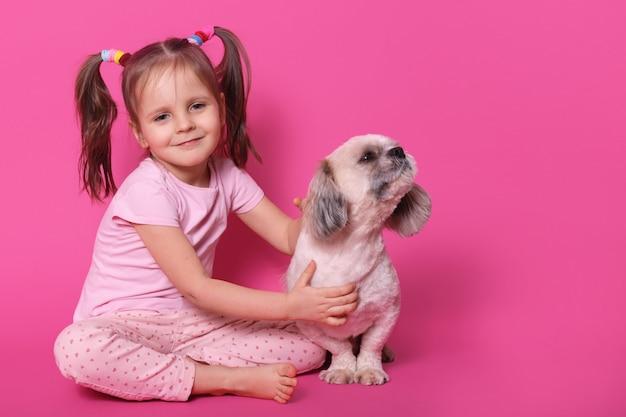 Lief schattig klein kind met twee grappige paardenstaarten, in een goed humeur, vrije tijd doorbrengen met huisdier, het dicht bij zich houden, puppy opzij kijken, ruiken, kalm zitten. copyspace voor reclame.