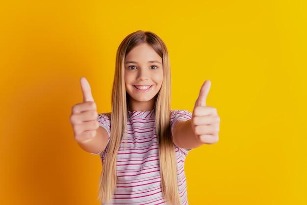 Lief steil haar pre-tiener meisje met thumbup geïsoleerd op gele achtergrond