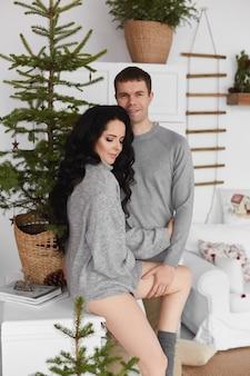 Lief stel jonge geliefden brengen de dag door in het interieur dat is versierd voor kerstmis