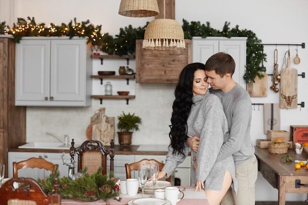 Lief stel jonge geliefden poseren in de ingerichte keuken op kerstochtend