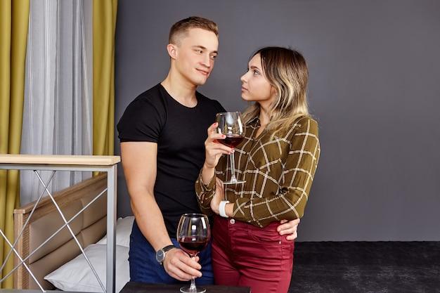Lief studentenpaar drinkt wijn in de slaapzaal tijdens een romantische date.