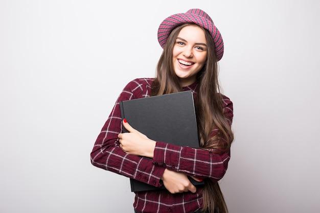 Lief vriendelijk jong studentenmeisje dat kleurrijke oefenboeken houdt die op witte muur worden geïsoleerd