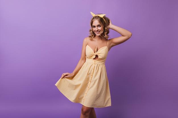 Lief vrouwelijk model in gele geruite jurk dansen met een glimlach. portret van spectaculaire blonde meisje genieten van een goede dag.