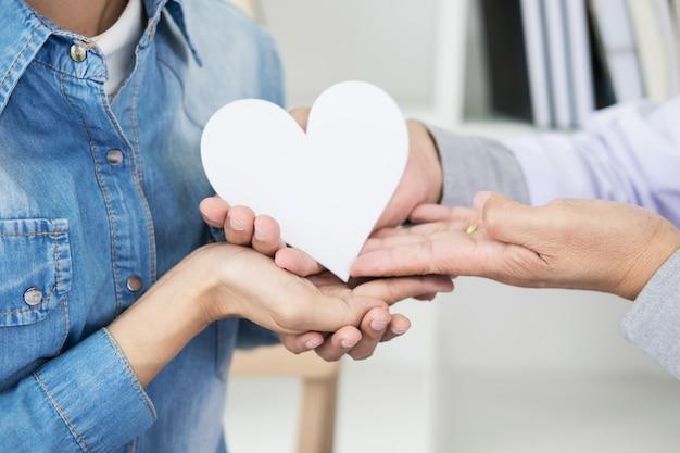 Liefdadigheidszorg, gezondheidszorg, donatie en medicijnconcept - arts man hand geven hart tot geduld