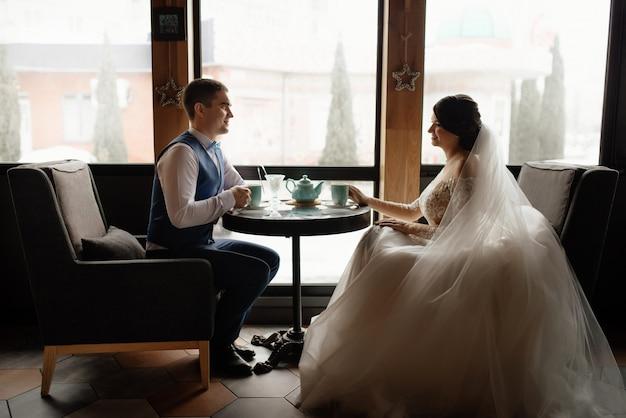 Liefde, bruiloft concept. gelukkig pasgetrouwde stel. liefdevolle jonggehuwden zitten tegenover het raam in het café, drinken thee en kijken elkaar aan