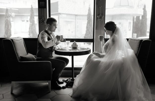 Liefde, bruiloft concept. gelukkig pasgetrouwde stel. liefdevolle jonggehuwden zitten tegenover het raam in het café en drinken thee.