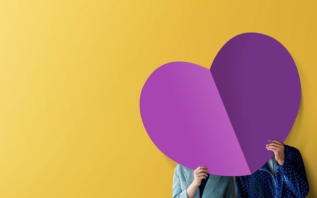 Liefde concept. jong koppel staande op de muur en bedekt gezicht door papier hart vorm
