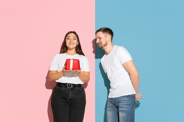 Liefde. een cadeau geven voor st. valentijnsdag. jonge man en vrouw in vrijetijdskleding op roze, blauwe tweekleurige muur. concept van menselijke emoties, gezichtsuitdrukking, relaties, advertentie. mooi koppel.