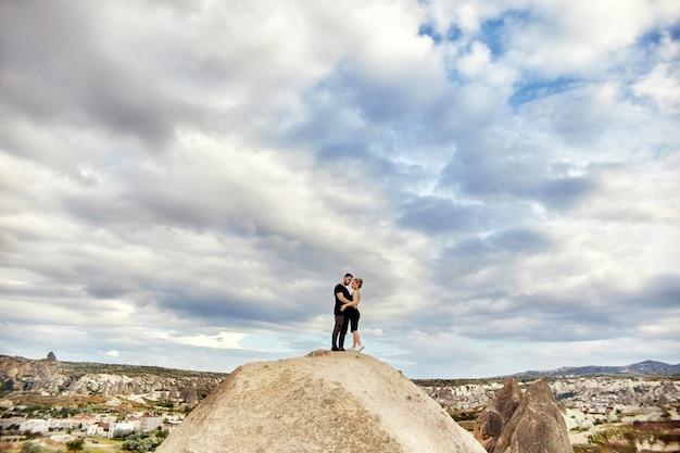 Liefde en emoties verliefde paar rusten in turkije. verliefd oost-echtpaar in de bergen van cappadocië knuffels en kusjes. close-upportret van een man en een vrouw. mooie halve maan oorbellen op meisjesoren