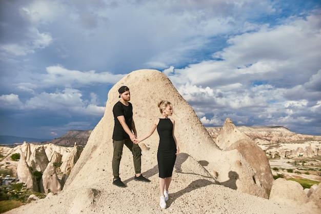 Liefde en emoties verliefde paar rusten in turkije. verliefd oost-echtpaar in de bergen van cappadocië knuffels en kusjes. close-upportret van een man en een vrouw. mooie halve maan oorbellen op vrouw oren