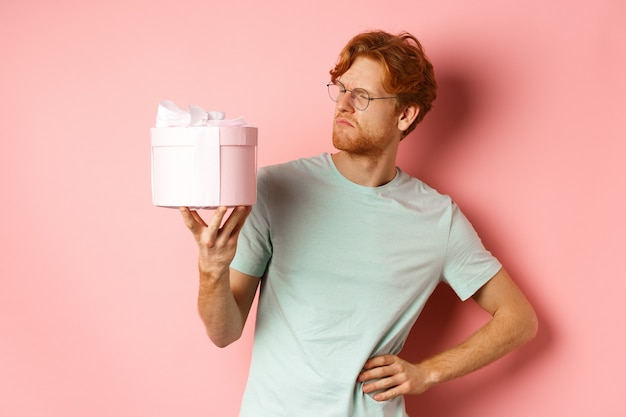 Liefde en vakantie concept. geïntrigeerde roodharige man kijkt verbaasd naar geschenkdoos, weet niet wat erin, staande over roze achtergrond.
