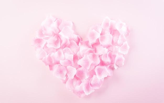 Liefde en valentijnsdag concept. roze harten gemaakt van rozenblaadjes op pastel achtergrond