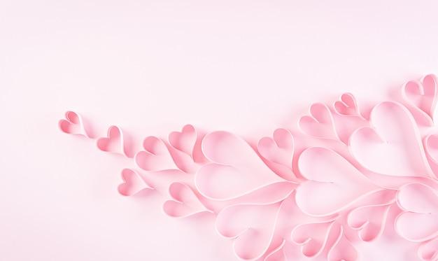 Liefde en valentijnsdag concept. roze papieren hartjes op pastel papier achtergrond