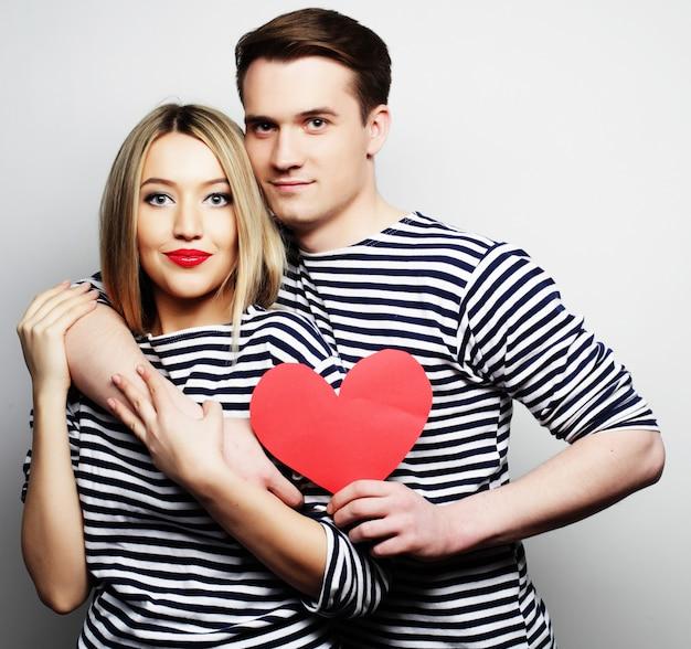 Liefde, familie en mensenconcept: gelukkige paar verliefd die rood hart houden