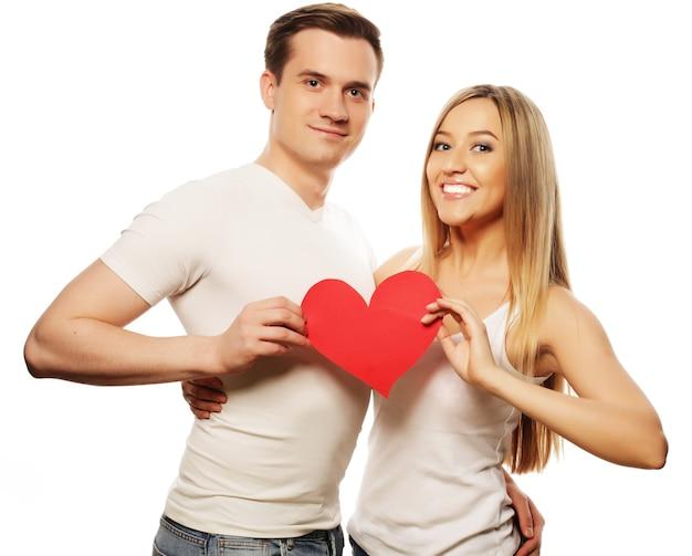 Liefde, familie en mensenconcept: gelukkige paar verliefd die rood hart houden.