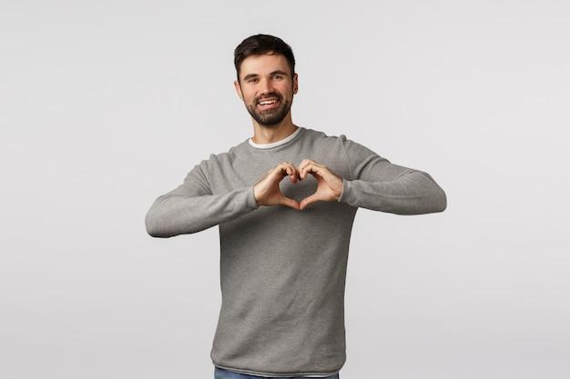 Liefde, familie en zorgconcept. charmante bebaarde vriendje drukt genegenheid en tedere gevoelens uit, laat hart ondertekenen over de borst en glimlachen, koestert relatie, aanbidt partner,
