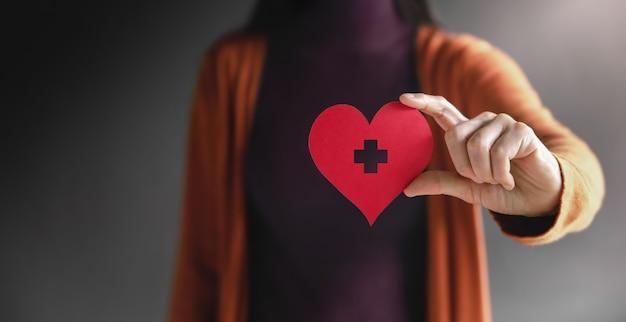 Liefde gezondheidszorg donatie en liefdadigheid concept close-up van vrijwillige vrouw met een hartvorm