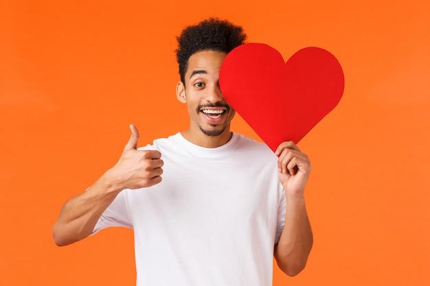 Liefde goed. charismatische afro-amerikaanse lachende man in wit t-shirt, romantische valentijnskaart vasthouden en duim opdagen, ware liefde gevonden in dating-app, vieren met vriendje, oranje
