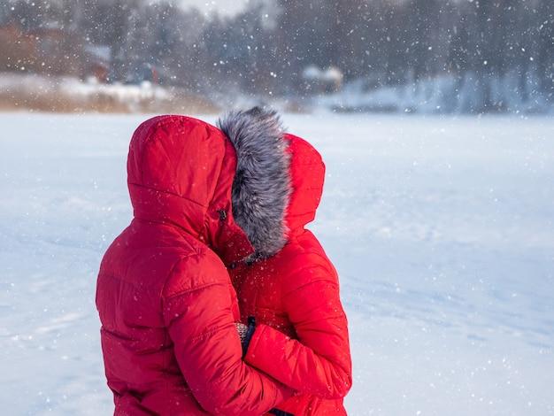 Liefde in de kou. een paar in rode jassen knuffelen in de sneeuw in de winter.