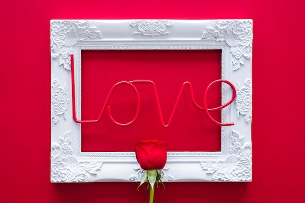Liefde inscriptie met frame en rose op tafel