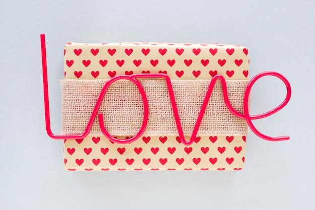 Liefde inscriptie met geschenkdoos op grijze tafel