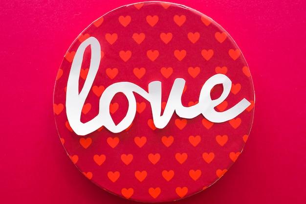 Liefde inscriptie met geschenkdoos op rode tafel