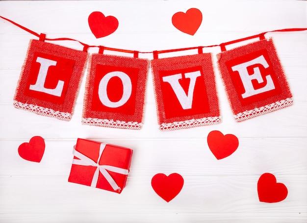 Liefde inscriptie met hartjes en geschenken op een houten witte achtergrond