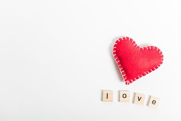 Liefde inscriptie met speelgoed hart op tafel