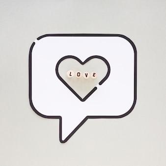Liefde inscriptie op bubble speech met hart pictogram op tafel