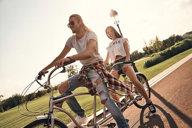Liefde inspireert hen. mooie jonge paar in vrijetijdskleding samen fietsen terwijl ze zorgeloze tijd buitenshuis doorbrengen