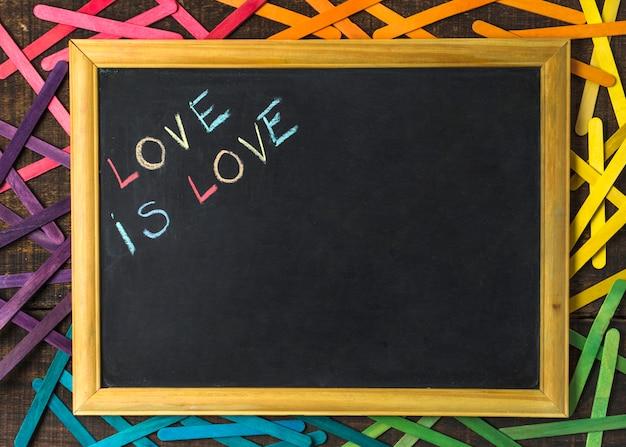 Liefde is liefdeswoorden op schoolbord tussen stokjes in lgbt-kleuren