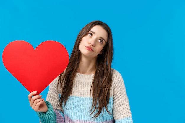 Liefde is voor sukkels. niet onder de indruk en ongestoord, achteloos aantrekkelijk universiteitsmeisje, oogrol en ongeïnteresseerd wegkijken, groot rood hart vasthouden, dongzorg op valentijnsdag, staand blauw