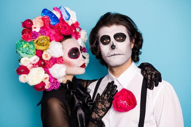 Liefde kan niet sterven. foto van griezelig eng paar man dame knuffelen wachten donker jagen prooi huwelijksreis diner dragen zwarte jurk dood kostuum rozen hoofdband bretels geïsoleerde blauwe kleur achtergrond