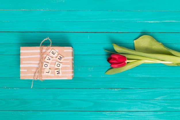 Liefde; mom; tekst op houten blok met geschenkdoos en tulp bloem