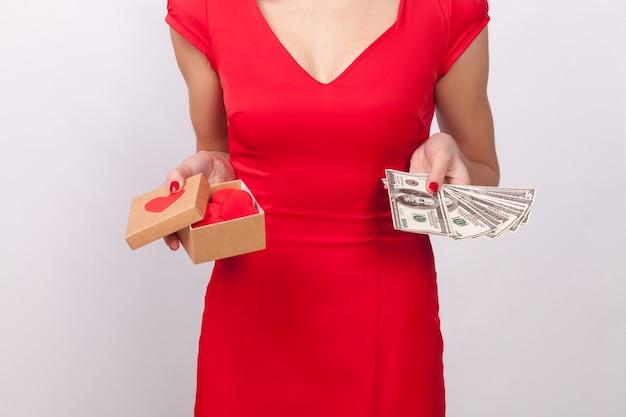 Liefde of geld. wat beter is, stelt vrouw in het rood voor. binnen, studio-opname, geïsoleerd op een grijze achtergrond